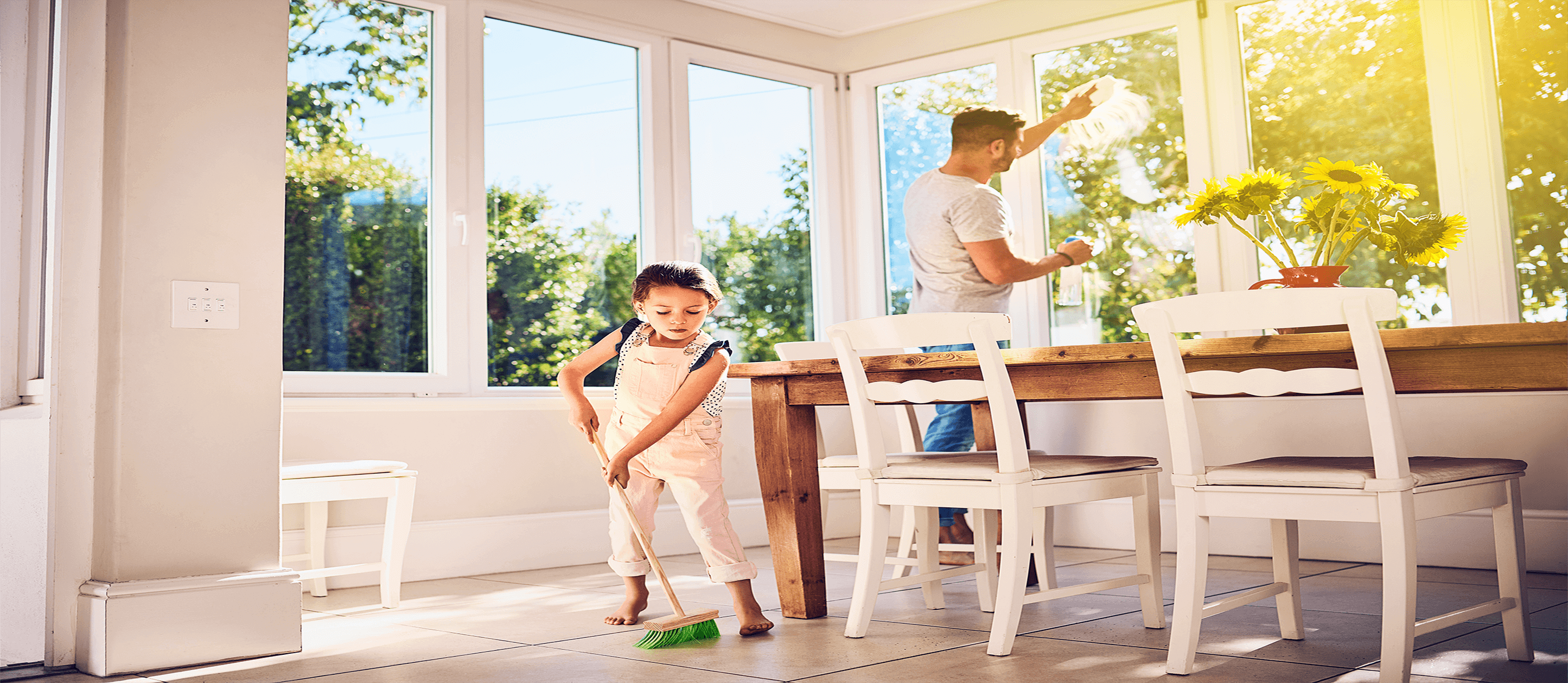 Image of child sweeping floor with dad cleaning windows