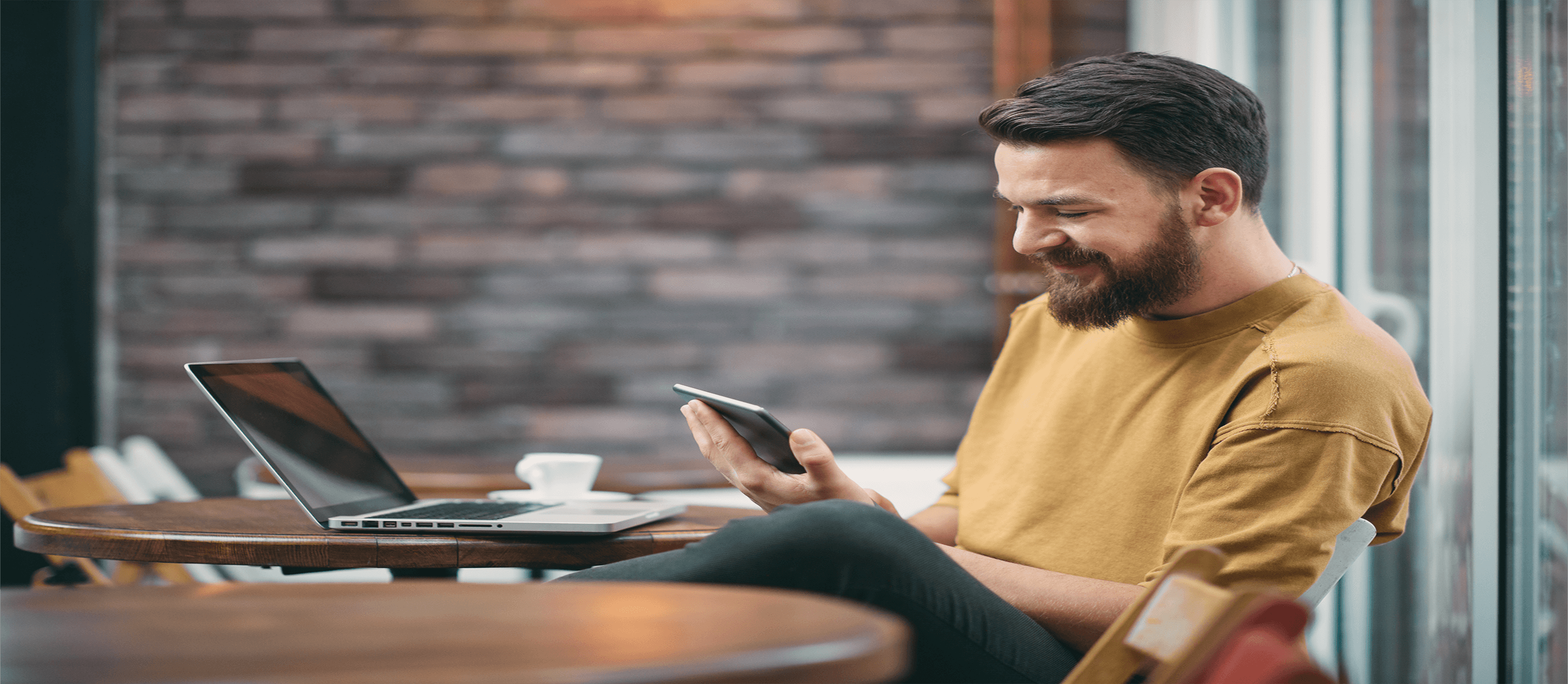 Image of man with laptop looking at smartphone