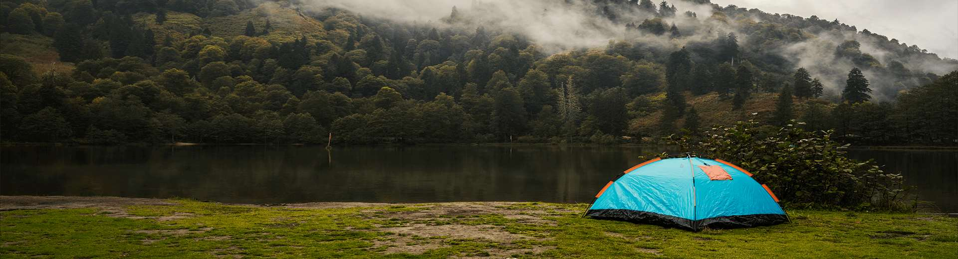 Image of camping tent beside lake and hillside
