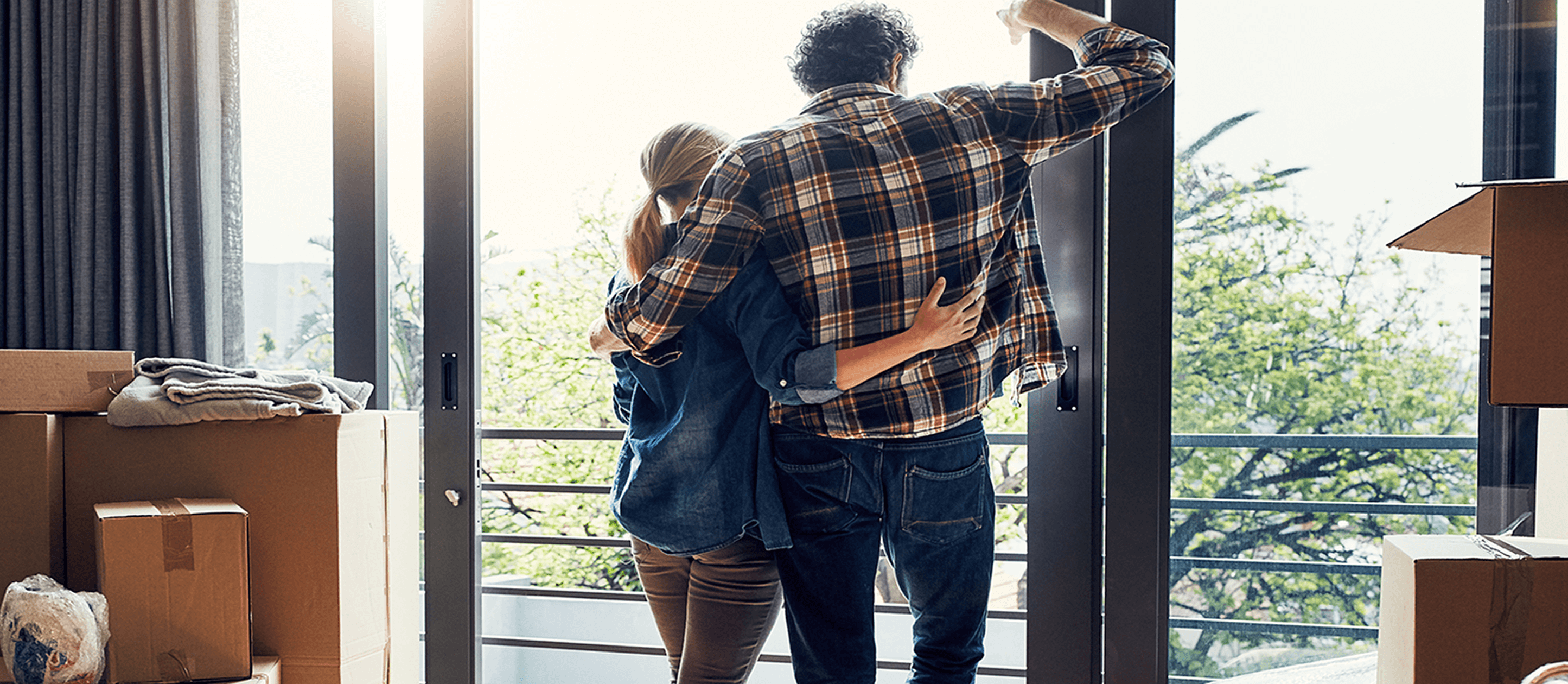 Image of couple surrounded by moving boxes and looking out of a glass door