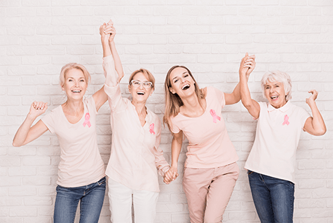 Image of four happy women holding and raising hands