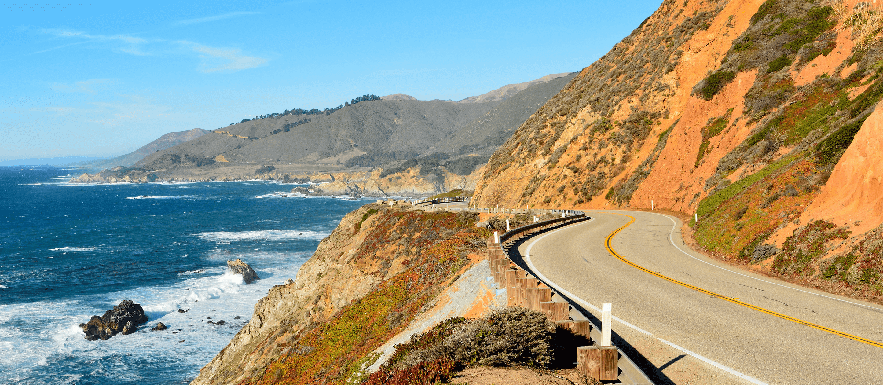 Image of winding road along the ocean with mountains in distance