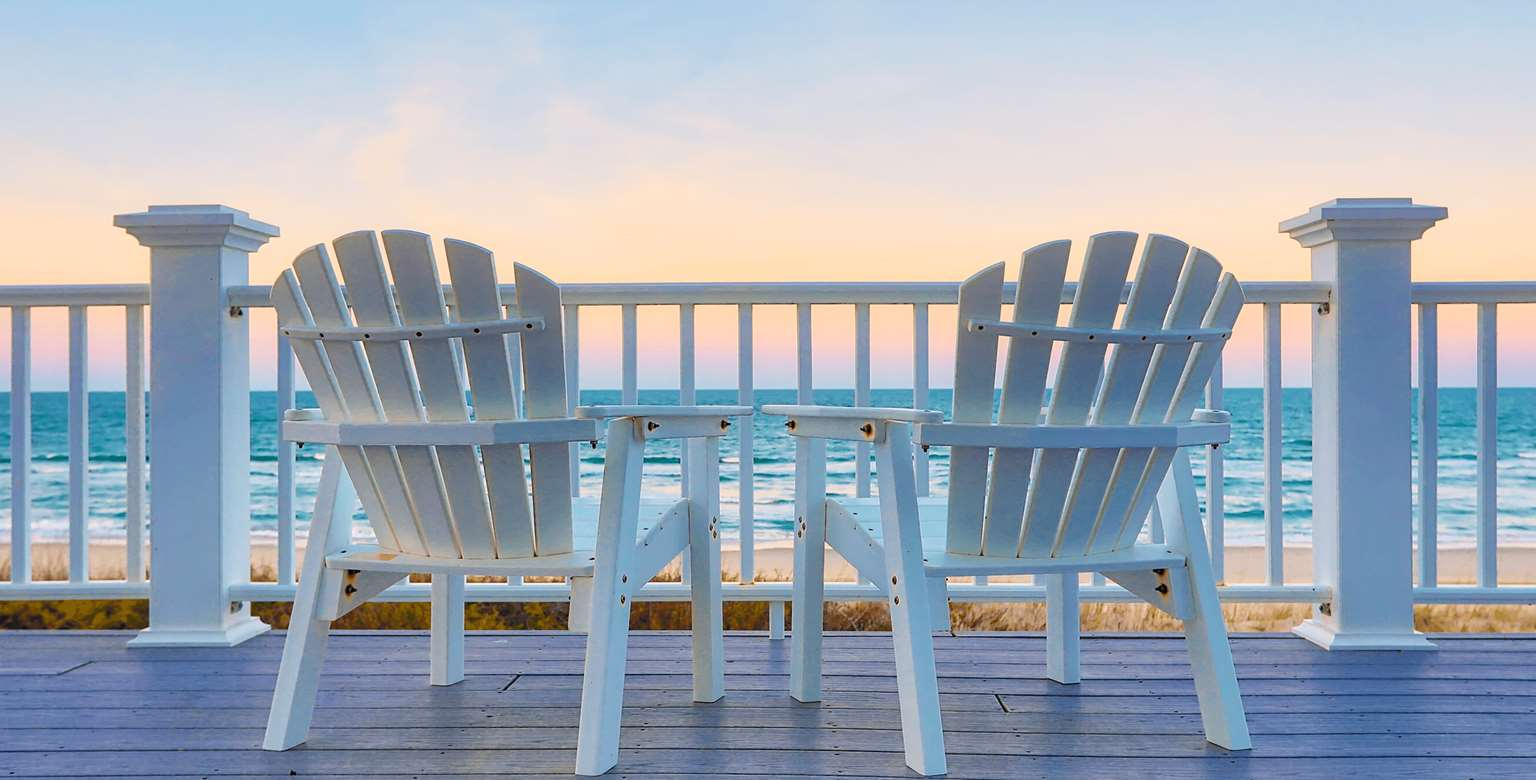 Image of chairs on a deck overlooking a beach at sunset