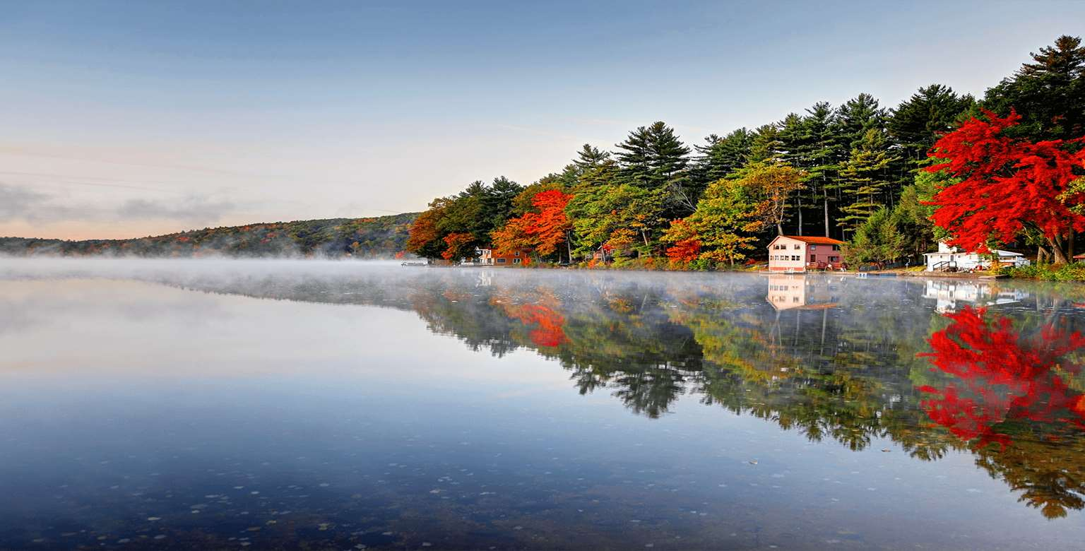 Image of clear lake surrounded by trees in autumn time