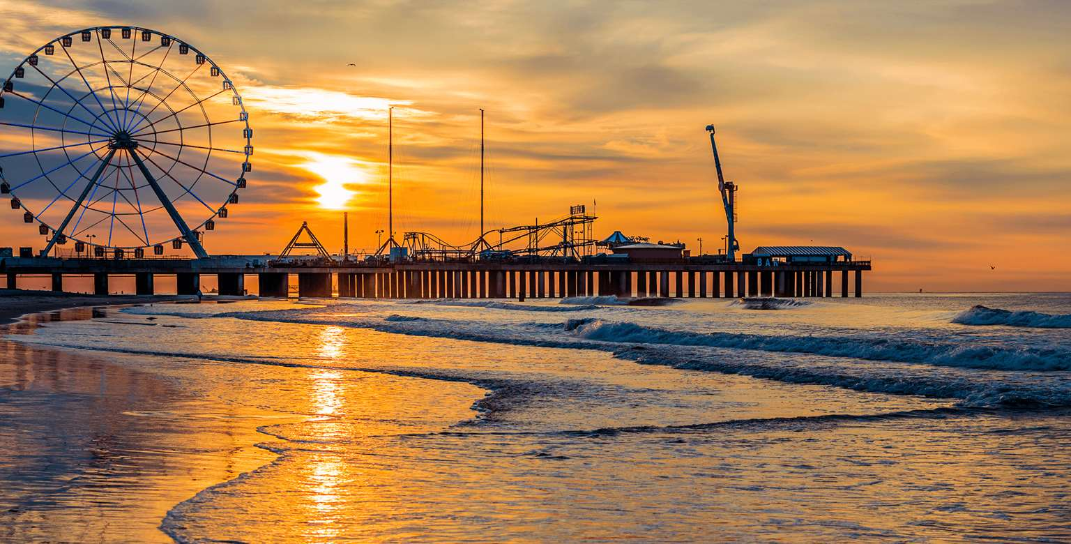 Image of ocean pier with ferris wheel at sunset