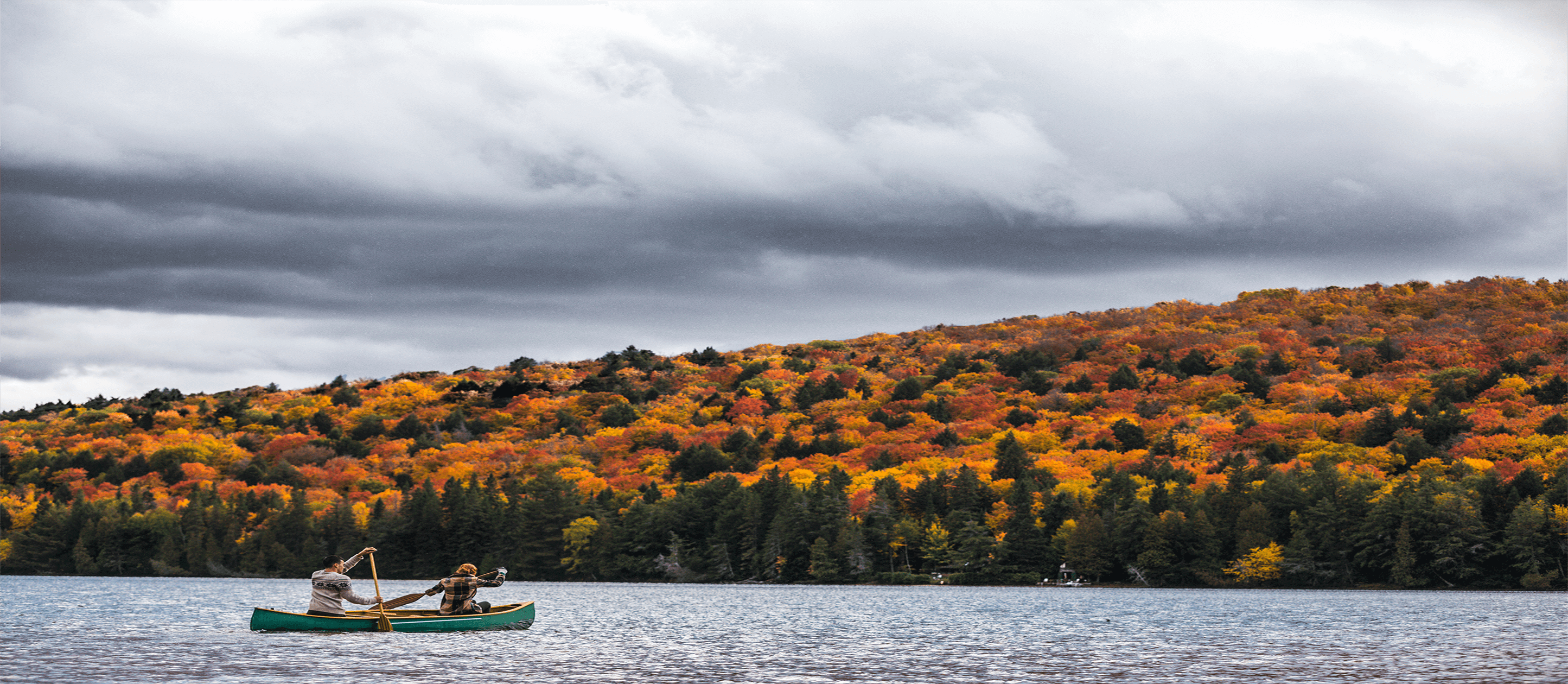 Image of canoe on lake with colorful trees surrounding