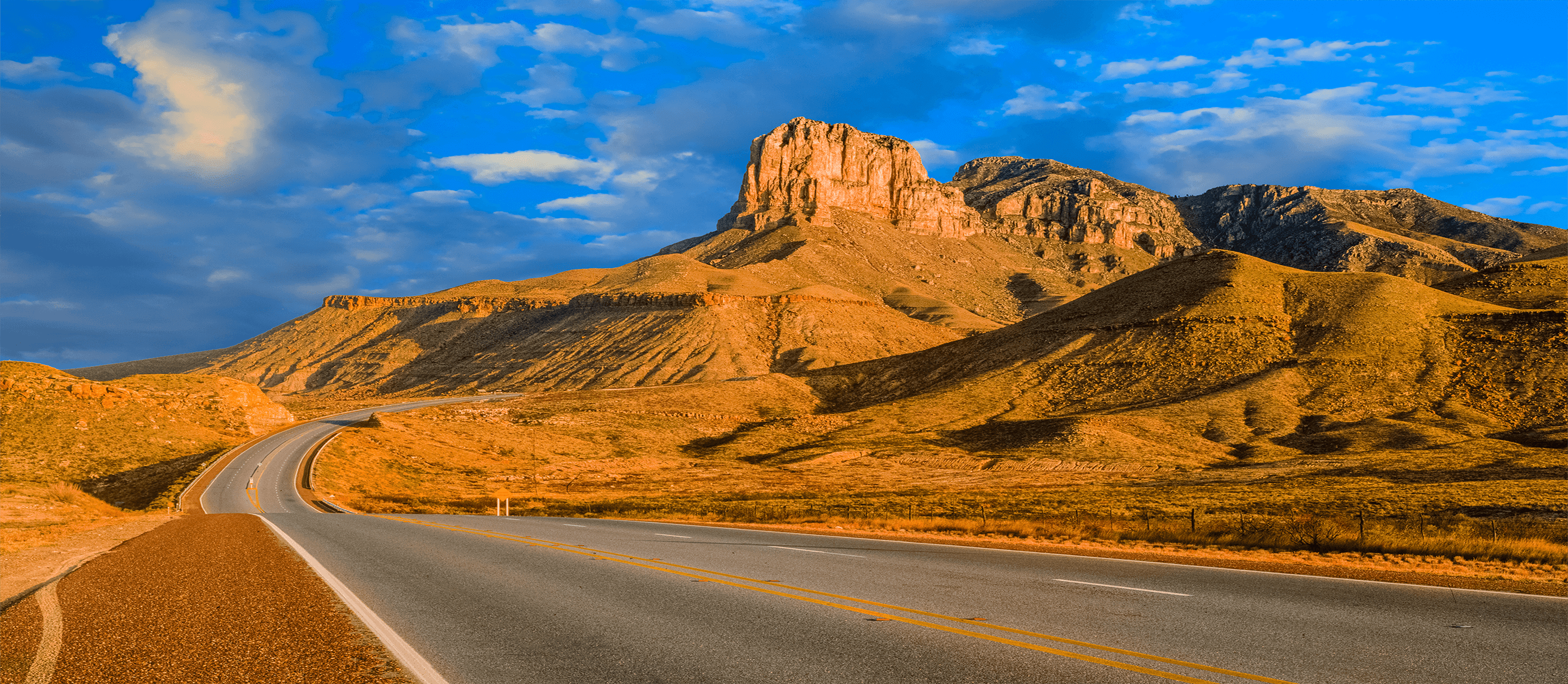 Image of winding road through desert with cliffs and blue sky