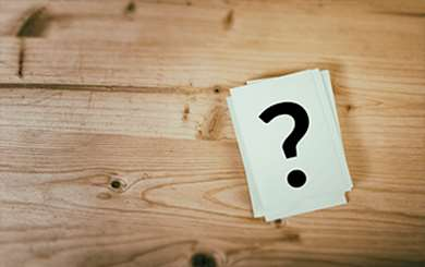 Wood background with white cards and question mark on it