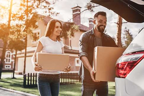 Image of a smiling man and woman carrying boxes to a car
