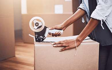 Image of person using packing tape to seal a moving box