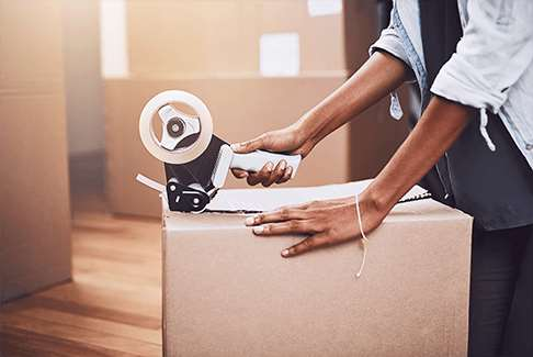 Image of a woman taping up a moving box