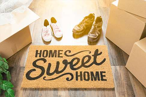 "Image of floor mat reading ""Home Sweet Home"" and surrounded by shoes and moving boxes"