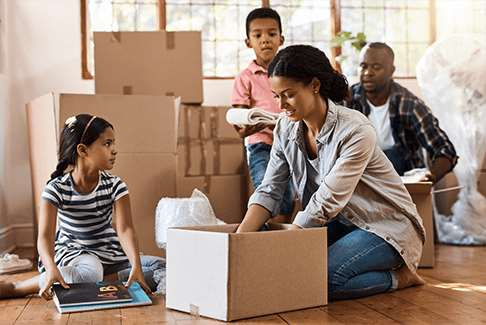 Image of family opening moving boxes inside new home or apartment