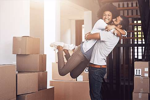 Image of happy man and woman hugging in front of packed storage boxes