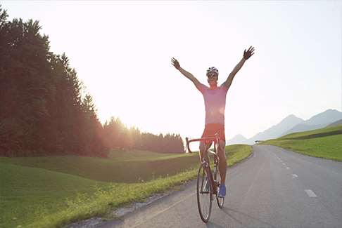 Image of happy man on bicycle on open road