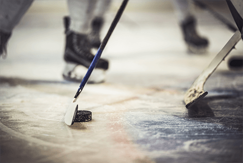 Image of ice hockey game in progress with closeup of hockey sticks and puck