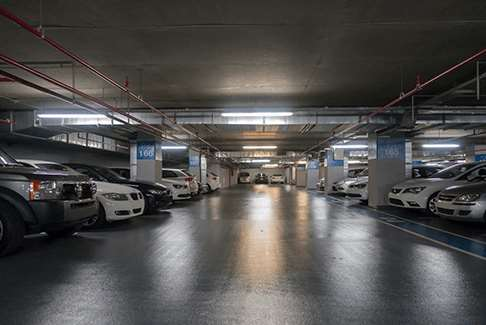 Image of an indoor parking garage filled with cars and trucks