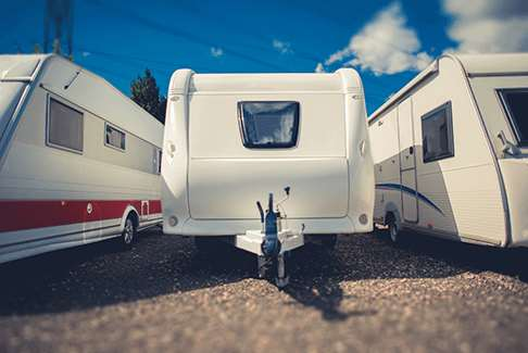 Image of three recreational vehicles parked outdoors