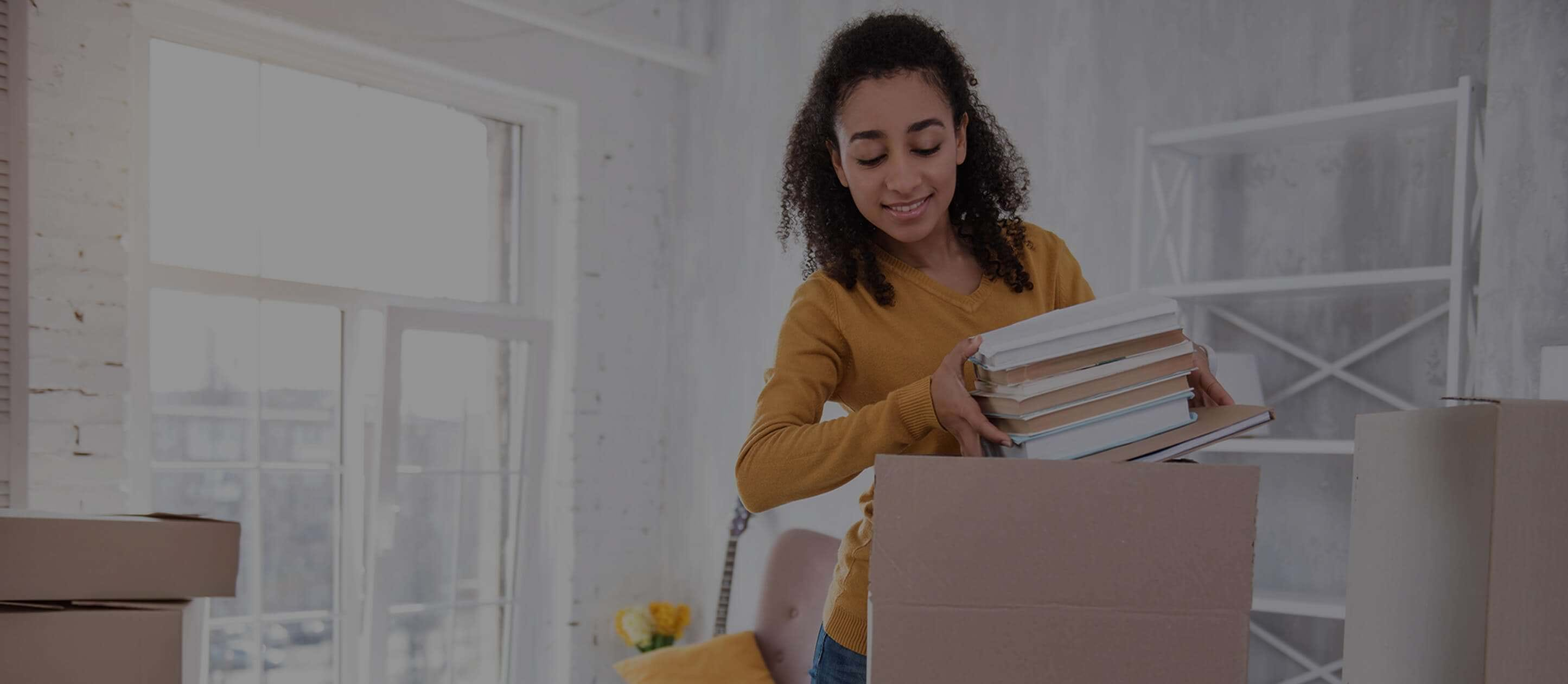 Image of smiling female student putting books into a moving box