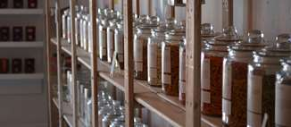 Multiple shelves of reusable glass jars filled with consumable supplies.
