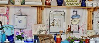 Display of random pottery and kitchen related items similar to table top display at an antique store or swap meet.