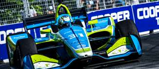 SmartStop Self Storage Indy Car, frontal view of car going about corner with driver Sage Karam.
