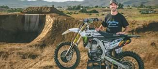 Bryce Hudson, Soap Boy, standing behind smartstop sponsored motorcycle for upcoming x-games
