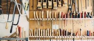 A picture of well-organized tools hanging on shelves and hooks a wall