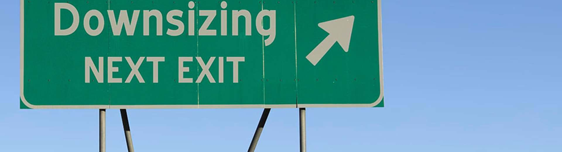 "There is a green street sign that says ""downsizing next exit"" while pointing to the right."