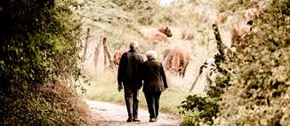 An older couple walks down a dirt road, arm in arm.
