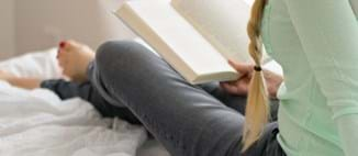 A student sits on her bed reading a book.