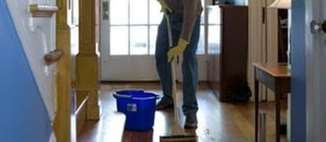 A man mops the entryway of his home.