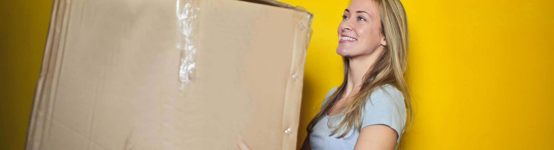 A woman holding a moving box.
