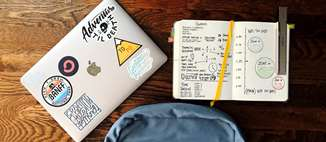 A backpack, laptop covered in stickers, and a notebook open to some hand-drawn grafts lay on a wooden table.