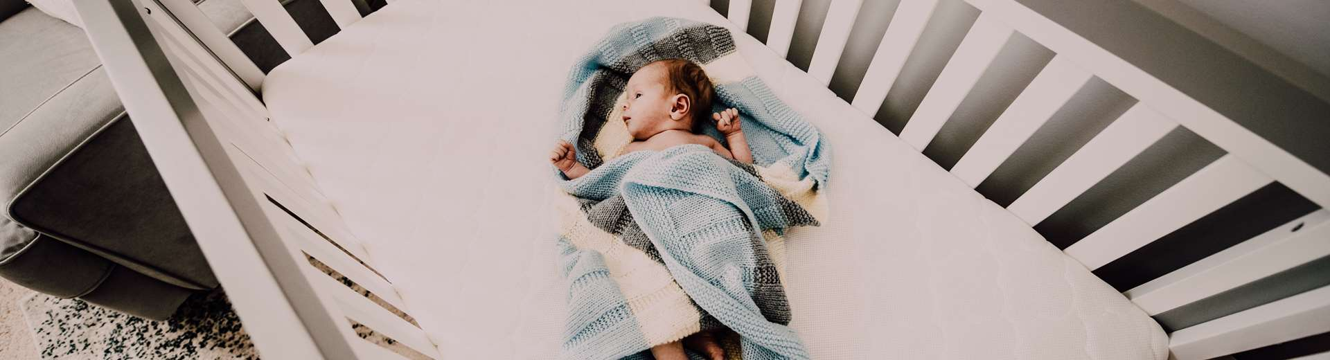 A baby wrapped in a blue blanket laying in a crib looking up at a mobile.
